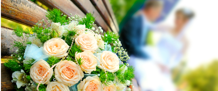 The beautiful wedding bouquet flowers lays on a bench, on a background a newly-married couple sit... Focus on a bouquet. Profile Adobe RGB (1998)